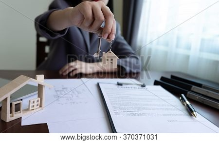 Real Estate Agent Or Home Seller Hand Holding House Key With A House Shaped Keyring On Table Office