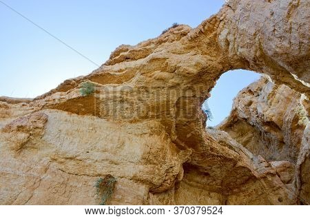 Ancient Cliffs Over The Kedron Stream. Israel, Palestine. Through The Hole In The Rock You Can See T