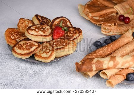 Old-fashioned Fluffy Pancakes And Crepe With Berries On Grey Background. Variety Of Pancakes. Thin A