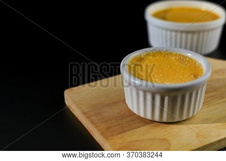 Close Up Homemade Creme Brulee In White Ramekin  With Sugar Top Up On Black Background With Copy Spa