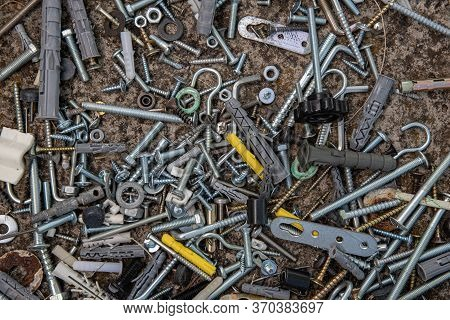 Pile Of Steel Bolts And Nuts, Hooks And Dowels On Grunge Stone Background With Copy Space. Soft Focu