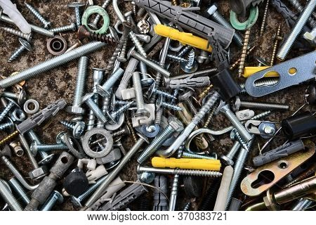 Flat Lay Of Steel Bolts And Nuts, Hooks And Yellow Dowels On Grunge Stone Background With Copy Space