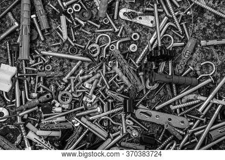 Black And White Photo Of Steel Bolts And Nuts, Hooks And Dowels On Grunge Stone Background With Copy