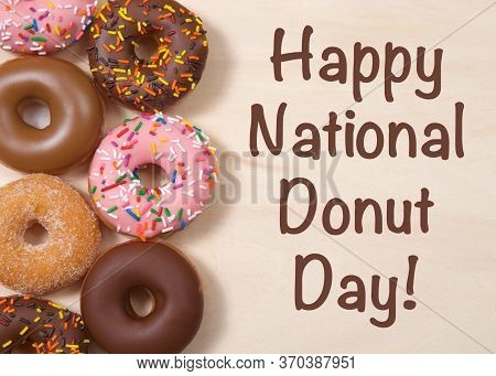 Flat Lay Top View Various Flavors Cake Donuts Frosted, Laying On Light Wood Table With  Happy Nation