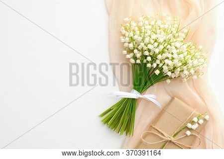 Spring Flowers Lily Of The Valley And Gift Box On White Table With Beige Cloth. Wedding, Mother's Da