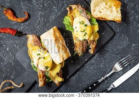 Sandwich With Eggs Benedict, Bacon And Salad On Black Stone Background