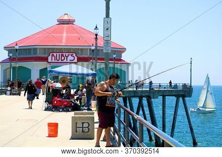 June 7, 2020 In Huntington Beach, Ca:  Sail Boat Sailing By Ruby\'s Restaurant On The Pier Where Peo