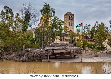 Qasr el-Yahud is the site of the baptism of Jesus Christ by John the Baptist. Church of John the Baptist on Jordan River. Jordanian national flags fluttering on coast.