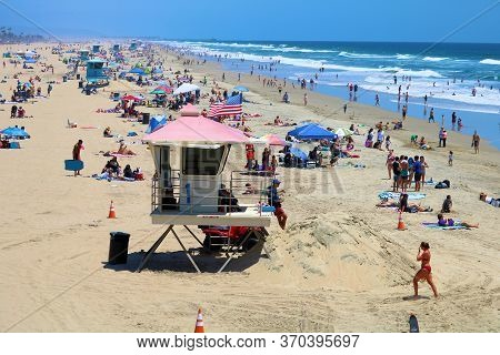 June 7, 2020 In Huntington Beach, Ca:  People Sunbathing On The Sandy Beach And Swimming In The Ocea
