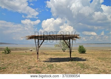 In The Photo A Shelter From The Sun With A Roof Made Of Reeds, On The Shore Of A Salty Estuary.