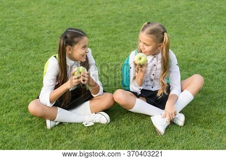 Back To School And Healthy Eating. Happy Kids Eat Apples On Green Grass. Healthy School Snack. Schoo
