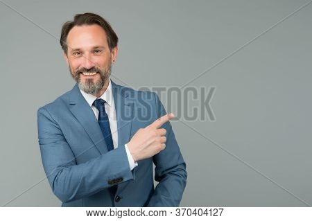 Look At This. Happy Boss Pointing Index Finger. Pointing And Promoting. Pointing At Grey Background.