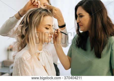 Professional Make-up Artist Making Face Makeup While Hairdresser Making Hair-do For Young Woman In B