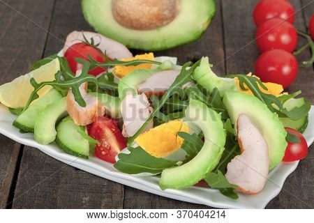 Avocado Salad With Rucola, Mixed Vegetables And Chicken  On Rustic Wooden Bowl. Healthy Food Concept
