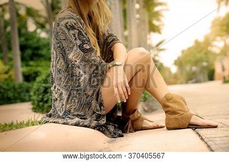 Bohemian woman sitting on side of road