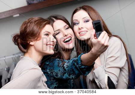Happy girls photo session on the cellphone after purchasing