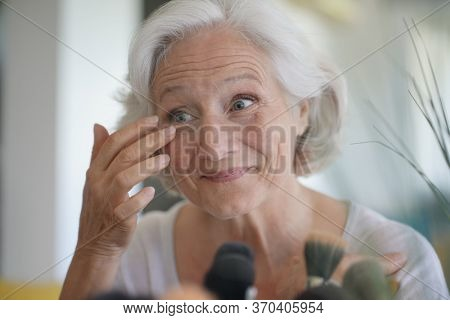 Portrait of senior woman taking care of her skin, looking at mirror
