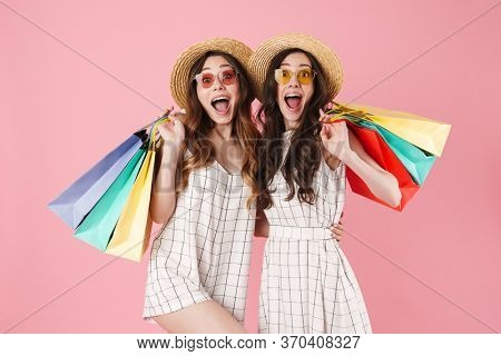 Image of excited women in straw hats holding sopping bags and hugging isolated over pink background