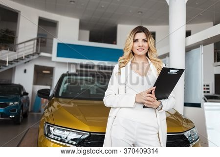 Portrait Of Saleswoman In Car Dealership. Business Lady Is A Representative Of The Car Dealership