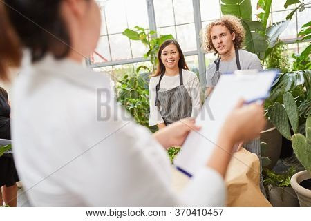 Examiner with clipboard and two florist trainees in the final exam