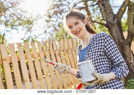Young woman as a craftsman trainee with paint can for painting wooden fence in the garden