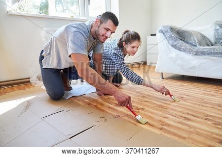 Do-it-yourself couple painting wood flooring Parquet in teamwork in new home