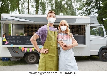 street sale and people concept - couple of young sellers wearing face protective medical mask for protection from virus disease at food truck