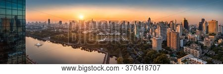 Wide Panoramic View Of Bangkok, Thailand. Cityscape With Public Park And Skyscrapers At Sunset.