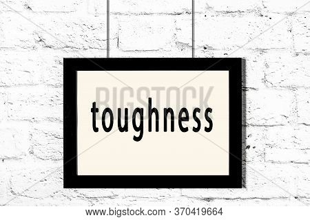 Black Wooden Frame With Inscription Toughness Hanging On White Brick Wall
