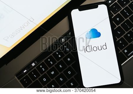 Hand Holding The Iphone With Apple Icloud Logo On The Screen. High Quality Photo
