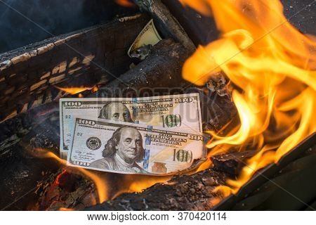Two Hundred Dollar Bills Are Burning In The Fire, Symbolizing The Recession Of The Economy, Crisis,