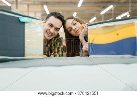 Couple choosing mattress in furniture store