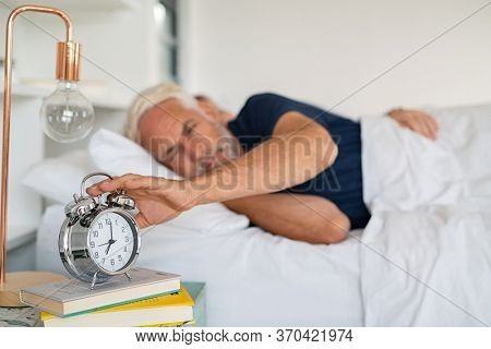 Old sleepy man lying on bed and stopping alarm clock. Senior man lying on side on bed turning off an alarm clock in the morning at 7am. Mature adult waking up in the morning.