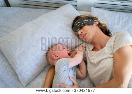 Tired mother with eye band trying to sleep while little toddler crying on bed. Angry baby boy crying and trying to wake mother. Stressed mother trying to take a nap with her child.