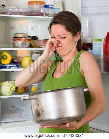 Young Woman Holding Foul Food Near Refrigerator At Home Kitchen.