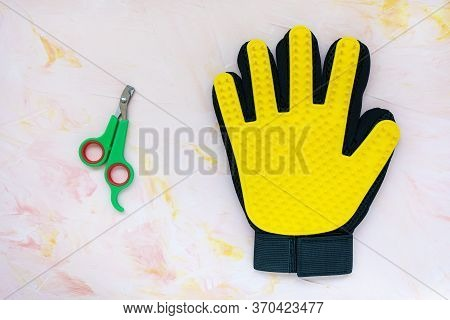 Yellow Silicone Glove And Nail Clippers For Cats And Dogs Grooming On Pink Background, Copy Space. P