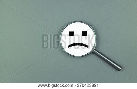 A Negative Smile Is Depicted On A Magnifying Glass. The Concept Of Depression, Ill Health, Failure,