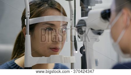 Woman checks her eyes in clinic