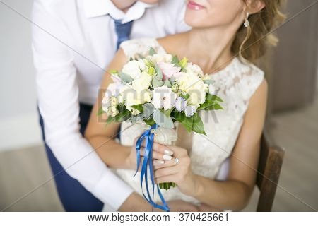 The Beautiful Wedding Bouquet From Roses With A Blue Tape Is Held In Hand By The Bride. Husband And