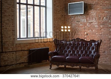 Claret Leather Sofa To The Loft An Interior With A Bright Searchlight And A Window. Brick Wall. Anci