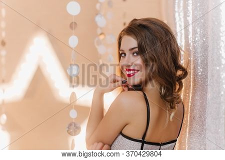 Crafty Lady With Red Lipstick Smiles Amiably On Brilliant Background. Woman With Curly Hair In Trend