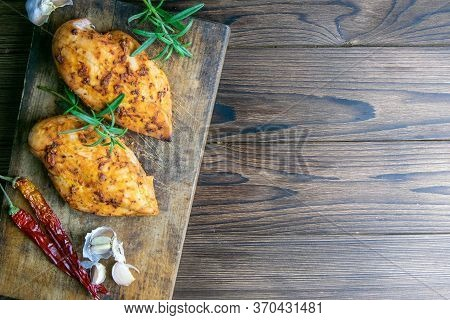 Baked Chicken Breast With Peper, Rosemary An Garlic On Wooden Cutting Board On Wooden Table. Top Vie