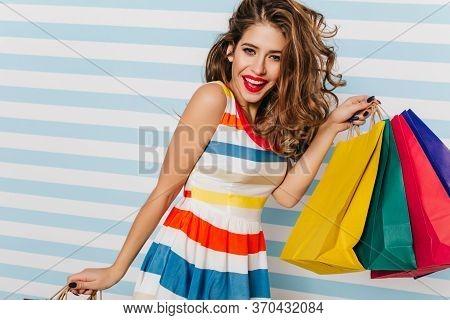Wonderful Caucasian Lady In Dress Posing During Shopping. Joyful White Woman With Long Hair Holding