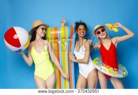 Pool Party. Three Cheerful Girlfriends In Swimsuits Posing With Inflatable Swim Toys Over Blue Studi