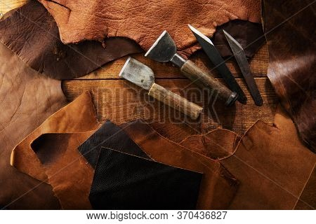 Leather craft or leather working. Leather cutting tools and selected pieces of tanned leather on craftman's work desk . Top view.