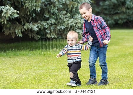 Two Playful Caucasian Brother Children Enjoy Having Fun Playing Together At Home Backtard Green Gras