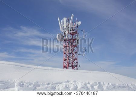 Communication Antenna In The Mountains. Broadcasting Tower Covered With Snow. A Radio Transmitter Fo