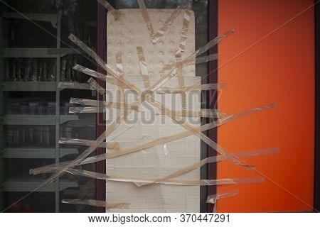 Broken Shop Window Taped With Tape And Cardboard. An Act Of Vandalism On The Street. A Randomly Brok