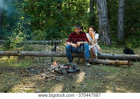 Couple In Love Having Picnic In The Country. Enjoying Camping Holiday In Countryside. Couple Camping