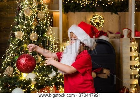 Cute Child Boy Decorating Christmas Tree. Happy Child With Christmas Bauble. Cute Little Kids Celebr